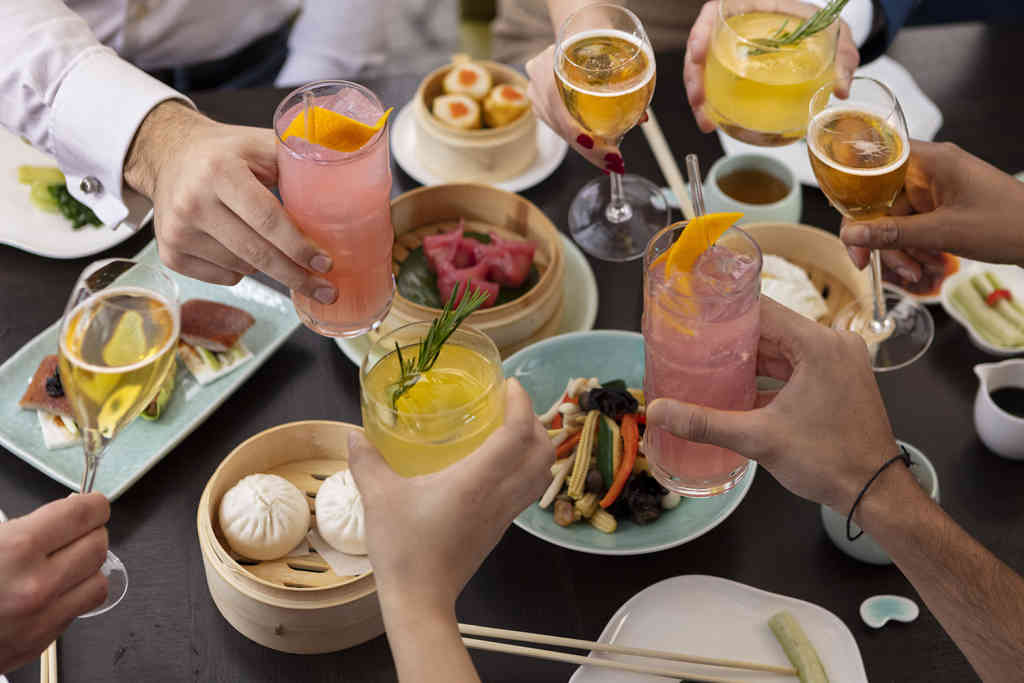 Group Dining with Various Cocktails and Dishes